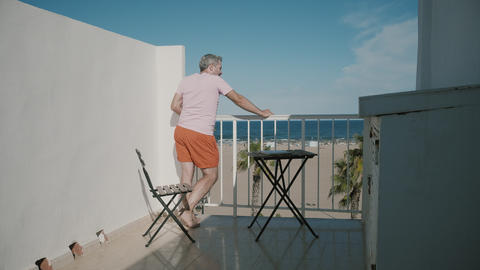 Man enjoys sea view from a hotel terrace on summer vacation Footage