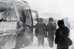 Passengers boarding on city bus during blizzard (snowfall) Photo