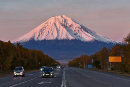 Cars drive along the road on background volcano at sunset sun Photo