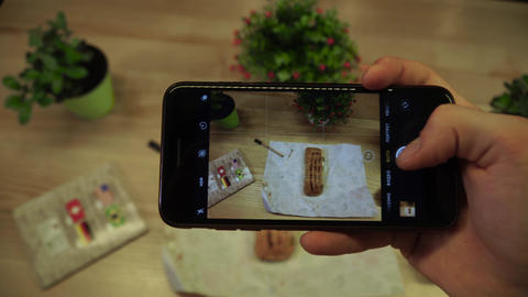 Female hand Taking Photos on smartphone of fresh mouth-watering roll with Footage