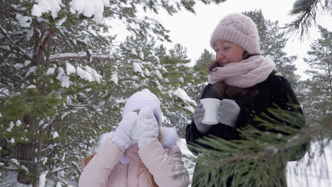 Mother and daughter drinking hot drinks in winter forest Footage