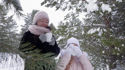 Mother and daughter drinking hot drinks in winter park Footage