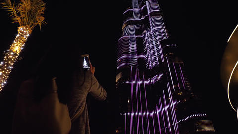 Girl shoot on her smartphone the Burj Khalifa tower at night Footage