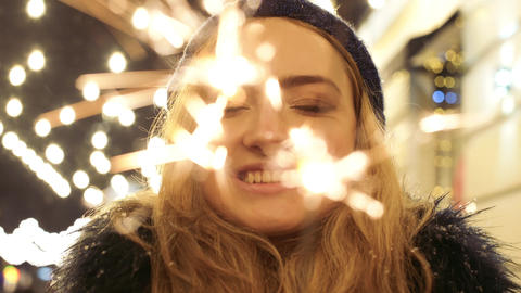Close up portrait of pretty smilling woman with sparklers in hands close up Live Action