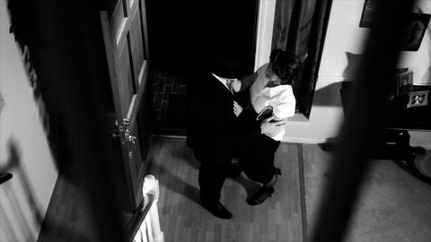 noir man walks in house and greets wife Footage