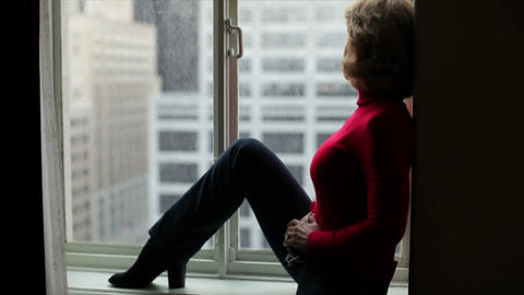 woman looking out a highrise window Live Action