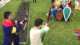 Historical reconstruction men shooting bows with arrows to knights behind shield Footage