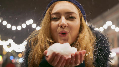 Portrait of cute young woman blowing on snow in her hands. Snow scatters in Live Action