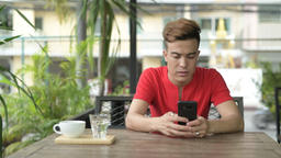 Happy young Asian man using phone at the coffee shop outdoors 영상물