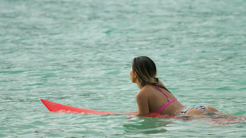 Attractive surfer woman on a surfboard floating in ocean GIF