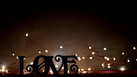 Silhouette of word love in a dark background lit by blinking of sparks Archivo