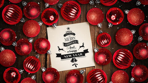 Falling snow and Merry Christmas text note and bauble decorations on wood Animation