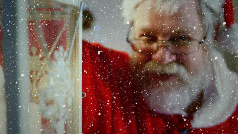 Video composition with falling snow over santa holding lattern Animation