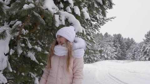 Young girl having fun in winter woods GIF