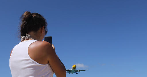 A girl is photographing a plane flying in the sky Footage