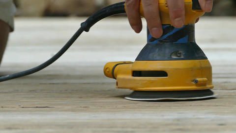 Sanding wooden deck outside with power sander in slow motion Archivo