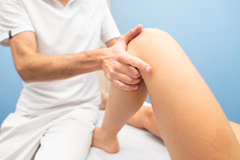 Physiotherapist performs knee drawer test to a woman Fotografía