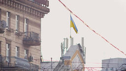 Street shot of building with Ukrainian flag flying on wind on sky and city Footage