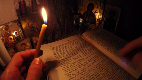 Monk reads the Bible and prays before the icons with candles Archivo