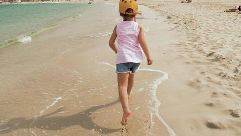 Little cute girl running along the beach Footage