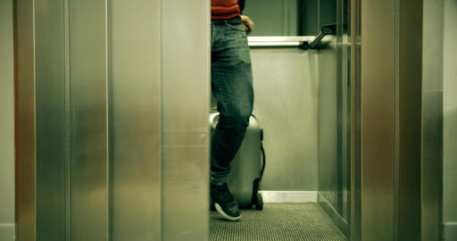 Man with suitcase exits from the hotel elevator Live Action