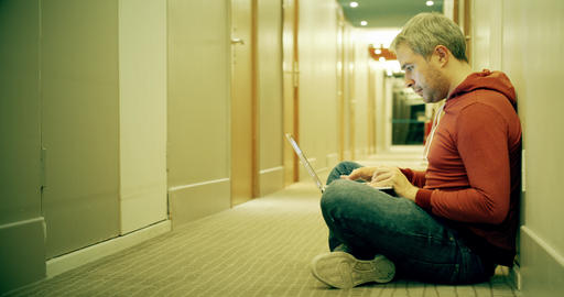 Smart grey haired man in casual clothes uses his laptop in the hotel hallway Footage