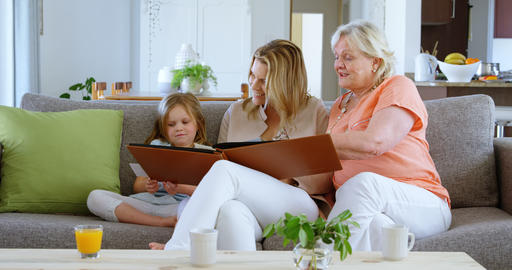Family looking photo album in living room 4k Live Action