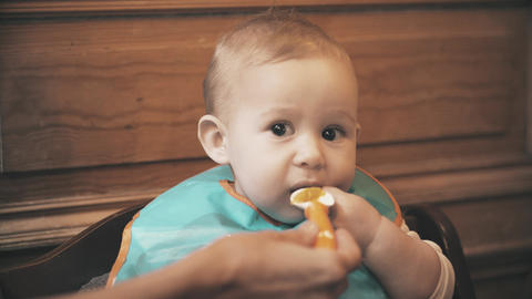 Funny baby girl eats unappetizing meal and frowns, close-up Live Action