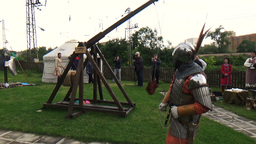 Medieval knight in full shining armory with helmet and steel sword fires old woo Footage