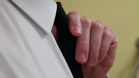 adjusting his tie closeup Live Action