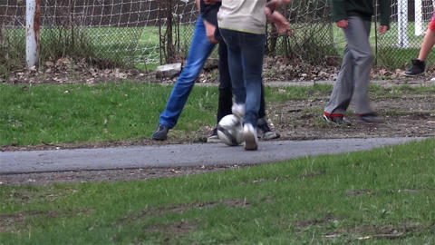 Group of youths playing football in the park on a driveway where passing cyclist Footage