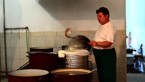 Cook who mixes in pots on the stove with a ladle located and strain the broth th Live Action