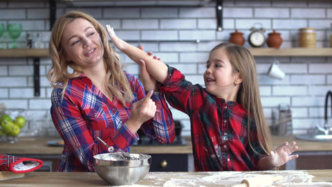 Carefree young mother and daughter fooling in the kitchen cooking at the kitchen Live Action