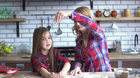 Carefree cute young mother and daughter fooling in the kitchen. Mom and child Footage