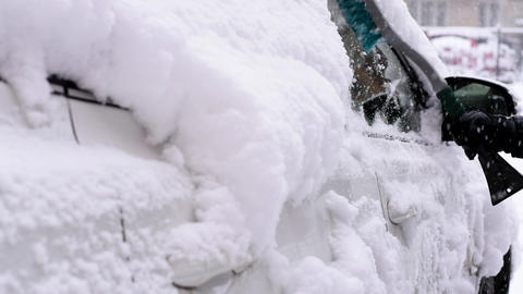 A man cleans a car from snow Footage