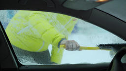 Scraping snow and ice from car windshield. Windshield wipers raised the night 영상물