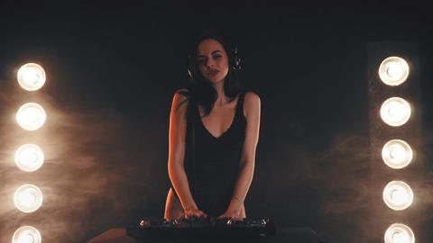 Girl DJ in headphones playing on turntables 영상물
