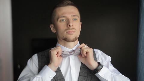 A man dresses and straightens a bow tie Live Action
