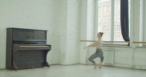 Ballet dancer exercising grand plie at barre GIF