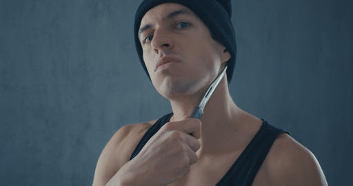 Portrait of Dangerous man in a cap with a knife Live Action