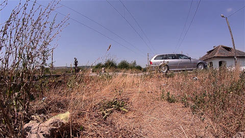 Railroad crossing where passing cars seen behind some dried weeds 65 Footage