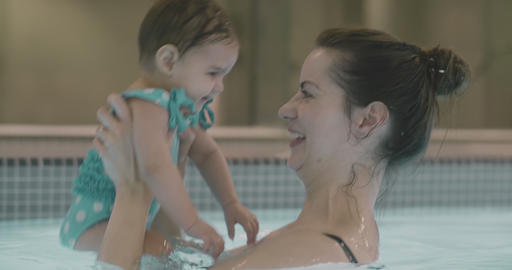 Mother playing with her baby girl in the pool 영상물
