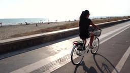 Girl walks by bike on the boardwalk Archivo
