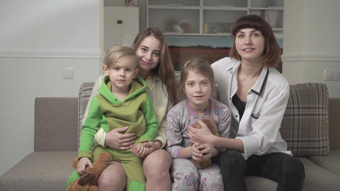 Cheerful happy family of four people sitting on sofa together. Family holiday Footage
