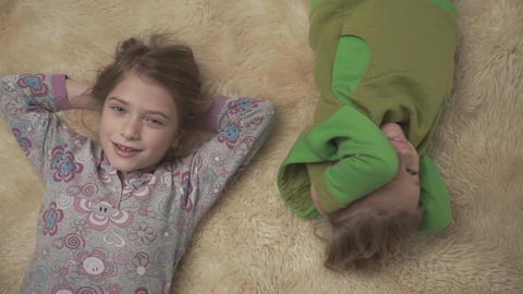 Adorable small kids in pajamas lying on the floor with fluffy carpet. Brother Footage