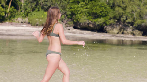 Carefree woman in swimsuit running on water at sea beach. Smiling woman enjoying Footage