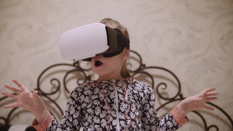 Little girl in VR headset looking up and trying to touch objects in virtual Live Action