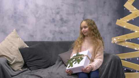 Girl with gift box sitting on a sofa Live Action