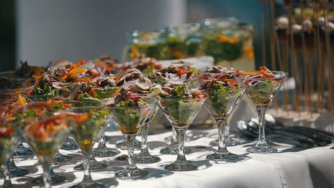 Reception table with wineglasses fillled with fresh salad. Focus panorama of Footage