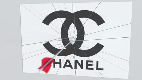 Archery arrow breaks glass plate with CHANEL company logo. Business issue Live Action
